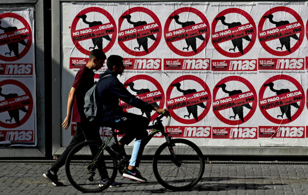 「債務返済にノー」と書かれたポスターの前を歩くブエノスアイレス市民(2月22日)=ロイター
