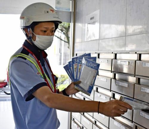 集合住宅のポストに配達されるマスク(23日午前、福井市)=共同