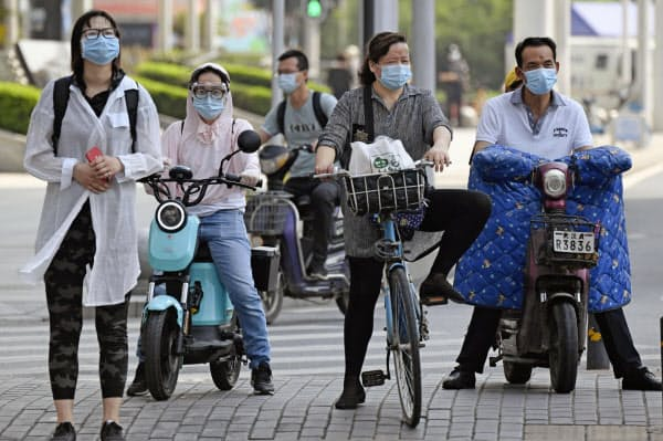 中国・武漢市内でマスクやゴーグルをした市民(23日、共同)