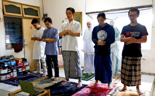 ラマダン明けに家の中で祈りを捧げるインドネシアの首都ジャカルタのイスラム教徒(24日)=ロイター