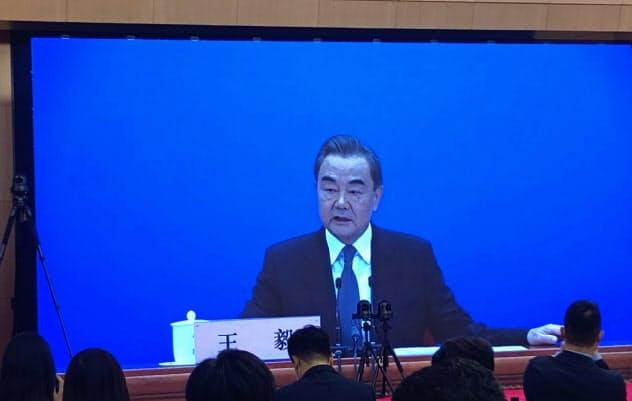 テレビモニターを通じて記者会見する中国の王毅外相(24日、北京)