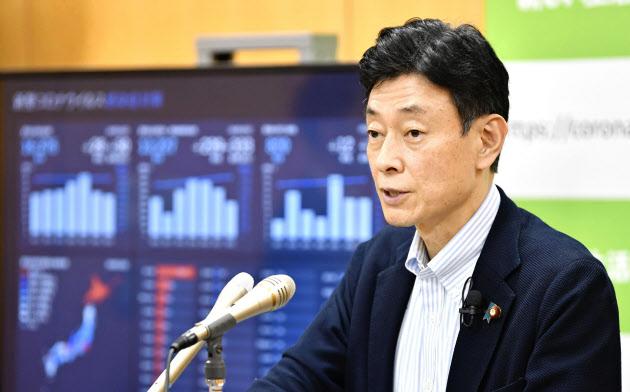 記者会見する西村経済再生相(24日午後、内閣府)=共同