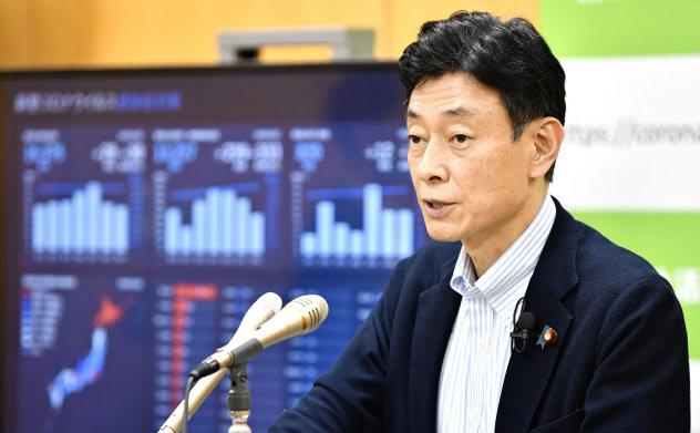 記者会見する西村経財相(24日、内閣府)=共同