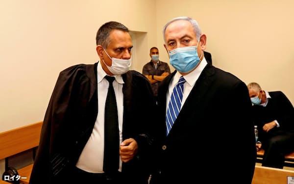 24日、マスクを付けて法廷に入ったネタニヤフ首相(右)(エルサレム)=ロイター