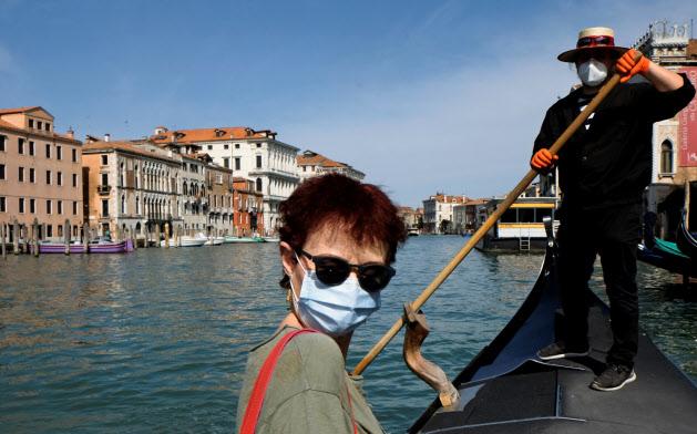マスク姿でゴンドラに乗るベネチアの観光客とゴンドリエーレ=ロイター