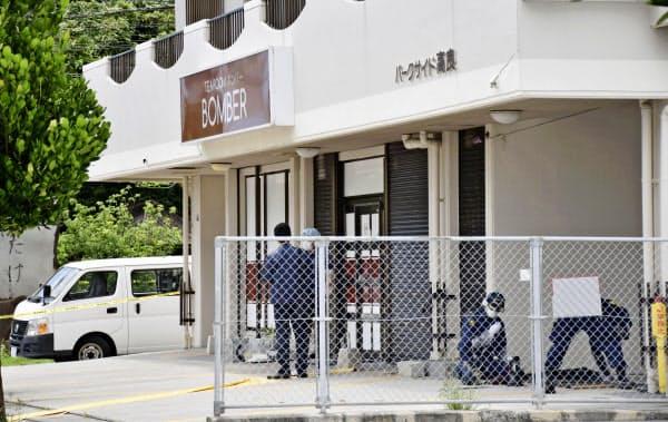 男女2人が切りつけられた喫茶店周辺を調べる捜査員ら(25日午前、那覇市)=共同