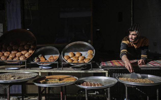 ラマダン向けのお菓子を販売するシリア人店主(同国イドリブで)=AP