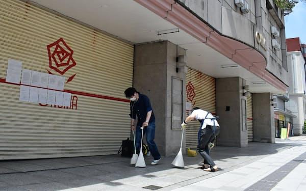 店舗周辺を清掃する大沼元山形本店長の道家英之さん(左)と元次長の武田仁さん(25日、山形市)