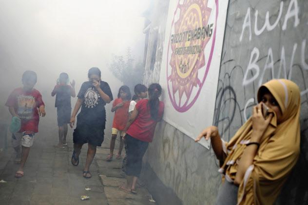 デング熱を媒介する蚊を殺す消毒剤がまかれ口をふさぐジャカルタ市民(3月)=AP