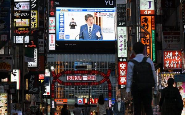 緊急事態宣言の全面解除を表明する安倍首相が大型ビジョンに映る(東京都新宿区)=野岡香里那撮影