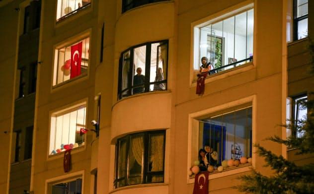 外出禁止中、国民議会発足を記念する「国民主権と子供の日」に窓辺から国歌を歌う人々(4月23日、アンカラ)=アナトリア通信