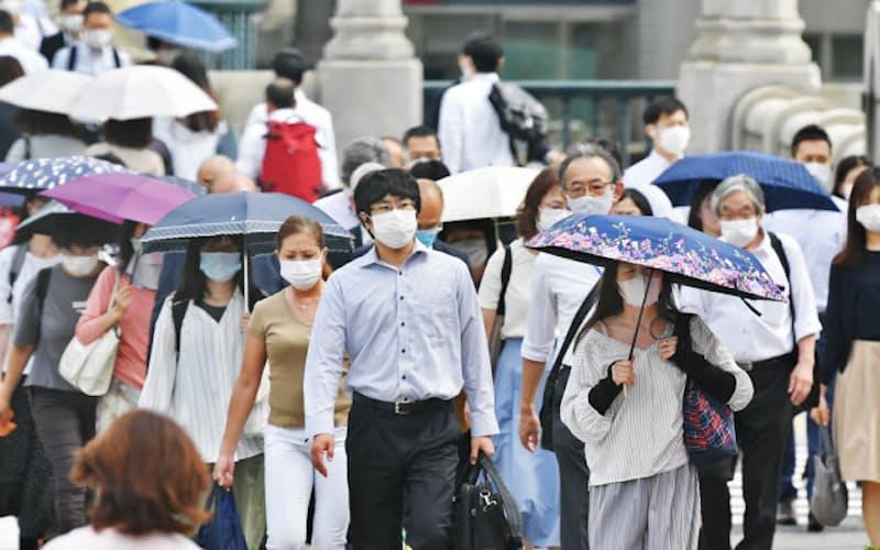 マスクを着けて出勤する人たち(25日、大阪市北区)