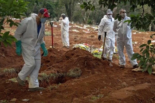 防護服を着て死者を墓地に埋葬する職員(8日、サンパウロ)