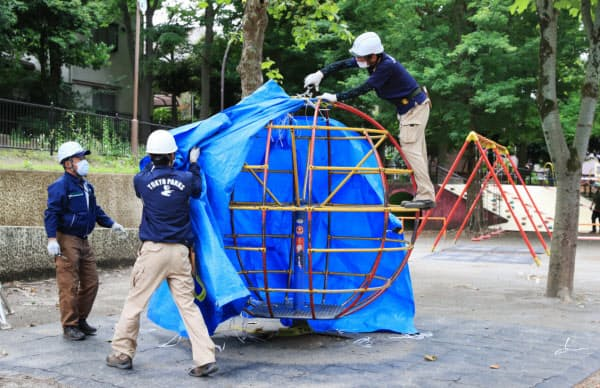 遊具に巻かれたブルーシートをはがす関係者(東京都世田谷区の駒沢公園)=三村幸作撮影