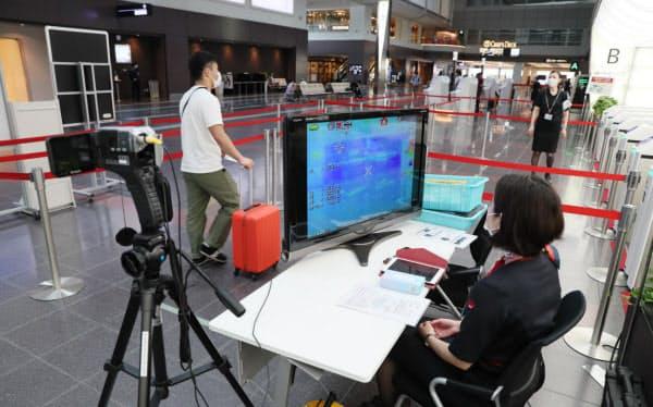 羽田空港の保安検査場前ではサーモグラフィーを活用し搭乗客の体温をチェック=樋口慧撮影