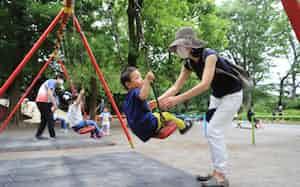 遊具で遊ぶ親子連れ(26日午前、東京都世田谷区の駒沢公園)=三村幸作撮影