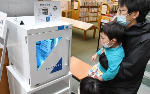 図書館で借りる本に紫外線を当て消毒する。時間は1分間(23日、茨城県日立市)