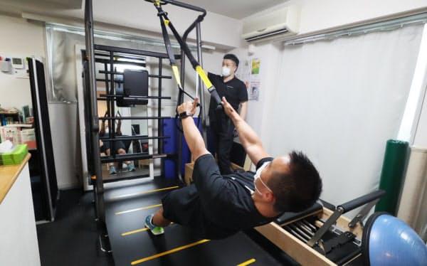 6月の営業再開に向け、新しいトレーニング機器の搬入と調整が進む個人向けジム(東京都中央区のオーワン銀座)=樋口慧撮影