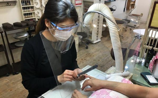 フェイスシールドを装着し施術するネイリスト(東京都渋谷区)