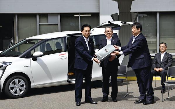 白根・トヨタ自動車東日本会長(中)らからレプリカキーを受け取る達増知事(左)(26日、岩手県庁正面玄関前)