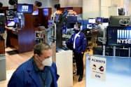 26日、マスクをつけて業務についたニューヨーク証券取引所のトレーダーら=ロイター
