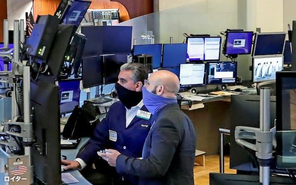 立会場の一部再開でトレーダーが戻った26日のニューヨーク証券取引所=ロイター