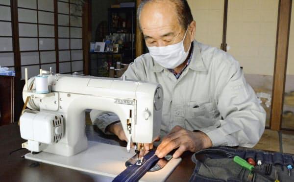 修理したミシンで試し縫いをする川副薫さん(19日、佐賀県神埼市)=共同