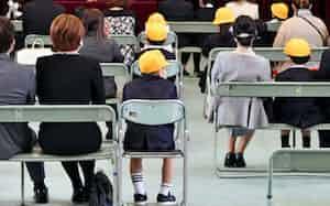 家族ごとにまとまり、間隔を空けて小学校の入学式に臨む新入生ら(4月4日、大阪市浪速区)