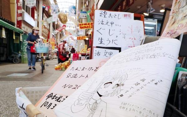アニメの舞台のモデルになった出町桝形商店街に置かれているファンらの交流ノート(27日午前、京都市上京区)