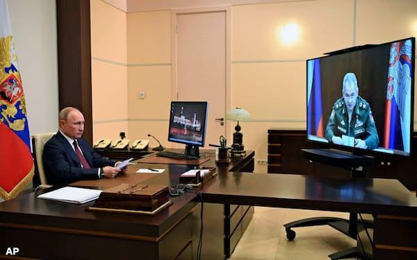26日、モスクワ郊外の公邸からテレビを通じ、対独戦勝75年の軍事パレードの準備をショイグ国防相に指示するプーチン大統領=AP