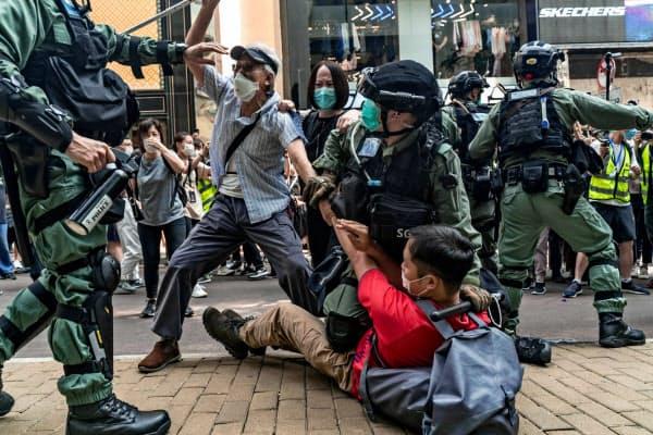 27日、香港のデモで、取っ組み合いになる警官隊とデモ支援者(ゲッティ=共同)