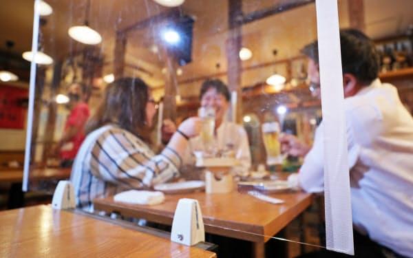 居酒屋に設置されたアクリル製の仕切り板「ソーシャルウォール」(27日、東京都港区)