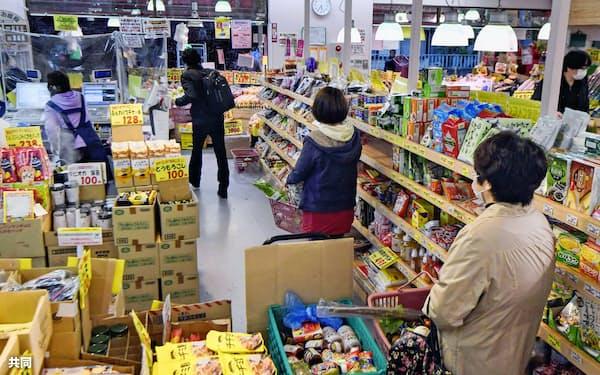 新型コロナウイルスの感染拡大防止のため、間隔を空けてレジを待つ買い物客(4月22日、東京都練馬区)