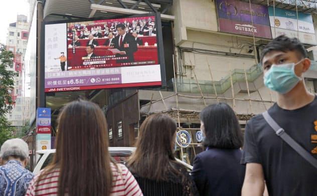 28日、香港の街頭で中国全人代を映す大型画面=共同