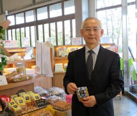 女性社員のアイデアが実を結んだパスタスナックを手にする斉之平伸一社長(同社店舗で)