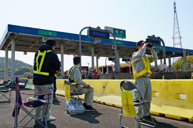 鳴門ICで県外ナンバー車をチェックする調査員(4月29日、徳島県鳴門市)