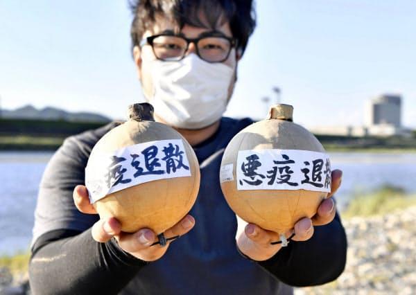 「悪疫退散」と書かれた花火玉と、打ち上げを企画した村瀬煙火の専務村瀬功さん(28日、岐阜市)