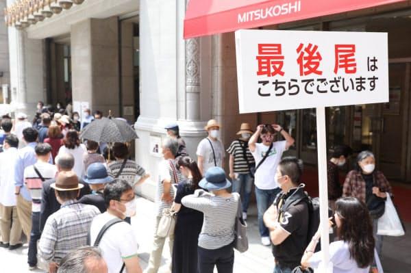 営業再開で日本橋三越本店に並ぶ人たち(30日、東京都中央区)