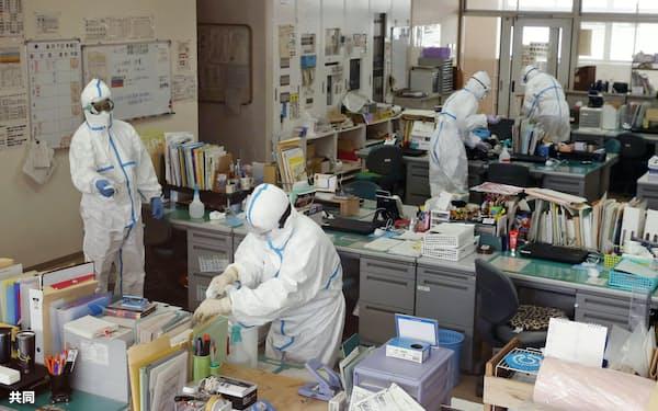 生徒の新型コロナウイルス感染が確認された、市立中学校の職員室を消毒する作業員(30日、北九州市)=共同