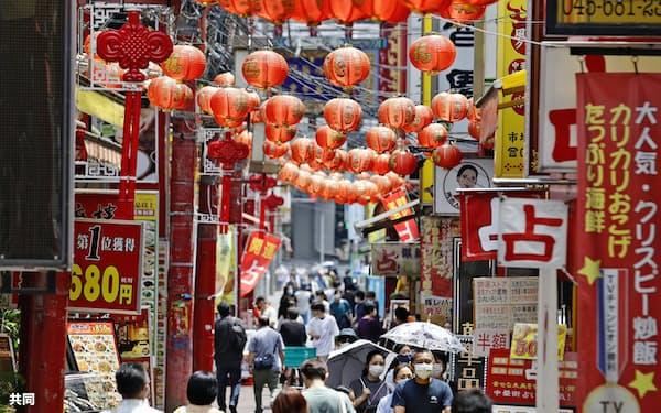 緊急事態宣言が解除されてから最初の週末を迎えた横浜・中華街を歩く人たち(30日午後)=共同