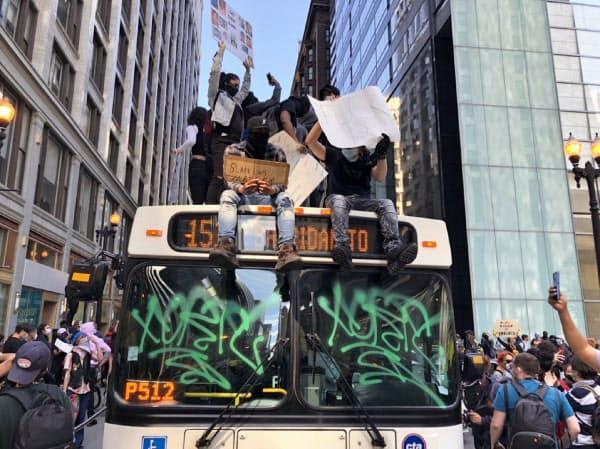 シカゴでは一部のデモ参加者が市営バスの屋根に上り、「正義がない限り、平和はない」と訴えた(30日)