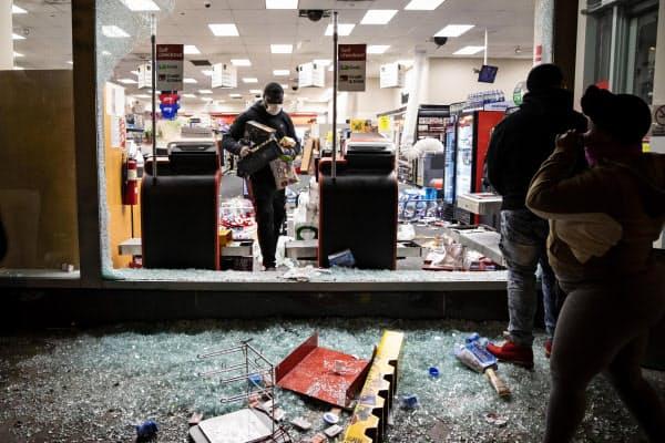30日、破壊された店舗に入るデモ参加者=米中西部イリノイ州(Ashlee Rezin Garcia/Chicago Sun-Times提供・AP=共同)