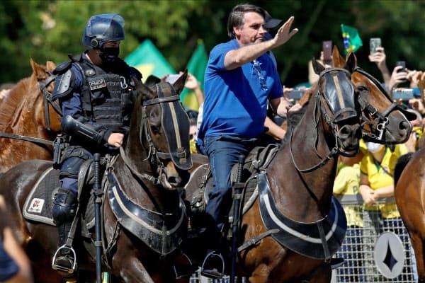 馬に乗り、支持者に手を振るブラジルのボルソナロ大統領(31日、ブラジリア)=ロイター