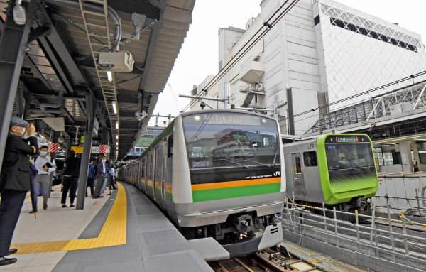 JR渋谷駅で運用が開始された新ホームを出発する車両(左)。右奥は山手線(1日午前)=共同