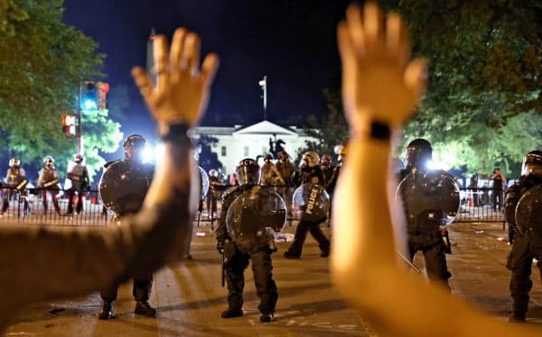 ホワイトハウス前で警察官に向け手を挙げるデモ参加者(5月31日、米首都ワシントン)=ロイター