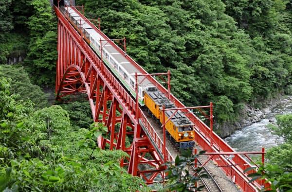 運行を再開し、鉄橋を渡る黒部峡谷鉄道のトロッコ電車(1日、富山県黒部市)=共同