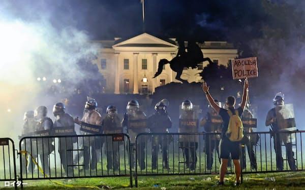 デモが過激化し、煙に包まれるホワイトハウス(5月31日、米ワシントン)=ロイター