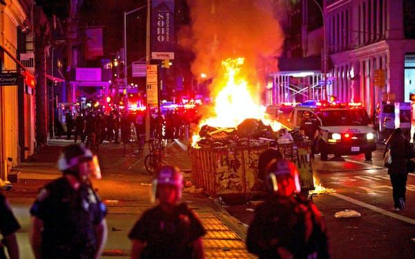 1日未明、ニューヨーク市マンハッタンで燃え上がるゴミ置き=ロイター