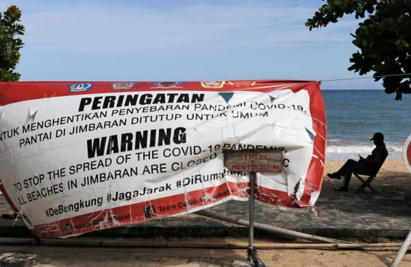 新型コロナウイルスの感染拡大を抑えるため閉鎖中と知らせる横断幕が張られたバリ島のビーチ(5月22日)=AP