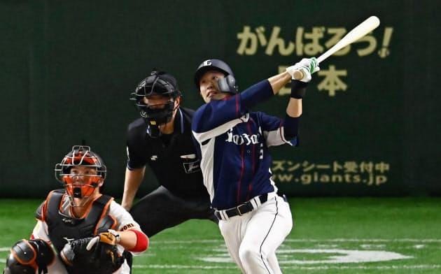 巨人との練習試合の7回、2ランを放つ西武・外崎。捕手炭谷(2日、東京ドーム)=共同